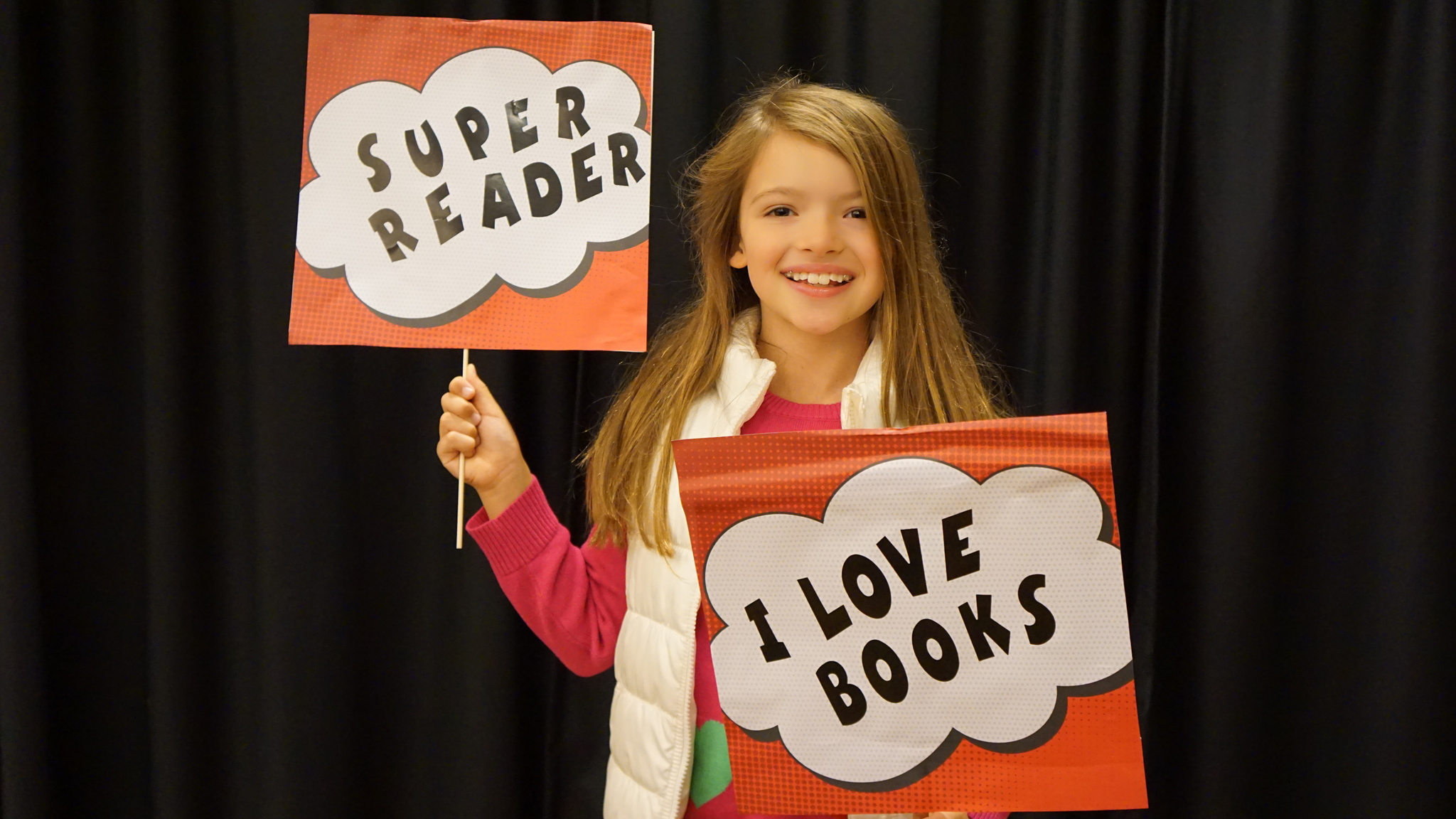 Girl holding signs saying Super Reader and I Love Books